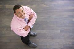 affärsman som ler inomhus plattform royaltyfria foton