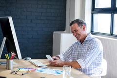 Affärsman som ler och använder en mobiltelefon Royaltyfria Bilder