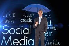 Affärsman som ler på det blåa paraplyet för kamera och för innehav Royaltyfri Bild