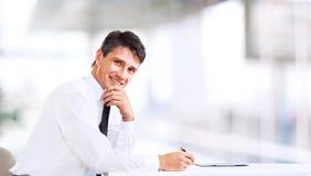 Affärsman som ler på kontoret Fotografering för Bildbyråer