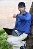 Affärsman som listar till musiken med bärbara datorn i en parkera Royaltyfri Fotografi