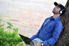 Affärsman som listar till musiken med bärbara datorn i en parkera Royaltyfria Bilder