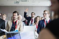 Affärsman som lyfter handen under seminarium Arkivfoto