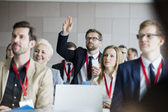 Affärsman som lyfter handen under seminarium på konventcentret royaltyfri bild