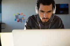 Affärsman som lyssnar till hörlurar, medan genom att använda bärbara datorn royaltyfria foton