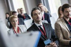 Affärsman som lyssnar till presentationen under seminarium arkivbilder