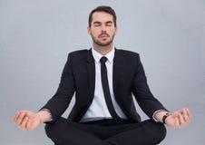 Affärsman som mediterar mot den gråa väggen Fotografering för Bildbyråer