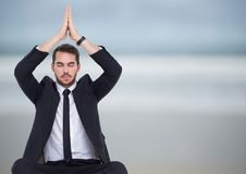 Affärsman som mediterar mot den oskarpa stranden Arkivbild