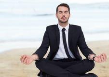 Affärsman som mediterar mot den oskarpa stranden Fotografering för Bildbyråer