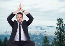 Affärsman som mediterar mot dimmiga kullar Arkivfoton