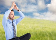 Affärsman som mediterar mot oskarp äng Royaltyfri Bild