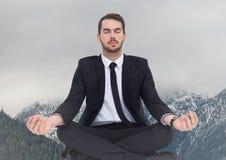 Affärsman som mediterar mot snöig berg Arkivfoto