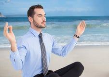 Affärsman som mediterar mot stranden Arkivfoton