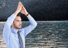 Affärsman som mediterar mot vatten och träd på kullen Arkivfoto