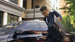 Affärsman som mottar goda nyheter och dansar och att tala på telefonen nära den lyxiga bilen lager videofilmer