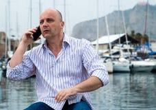 Affärsman som nästan talar på telefonen den lyxiga hamnen arkivbilder