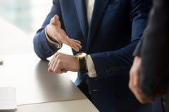 Affärsman som pekar på armbandsuret, punktlighet, tidledning Arkivbild