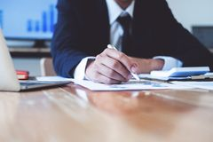 Affärsman som pekar på dokument, redovisande finansiell affärsrapport och bokföringdokument med räknemaskinen på skrivbordet på k arkivfoton