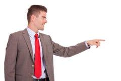 Affärsman som pekar till hans sida royaltyfria bilder