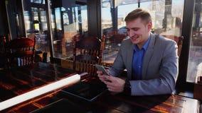 Affärsman som pratar på kafét vid smartphonen nära minnestavlan n lager videofilmer