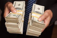 affärsman som räcker pengar över buntar arkivbild
