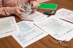 Affärsman som räknar dollar av skattformer Arkivfoton
