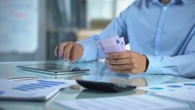 Affärsman som räknar euro och planerar företagsbudgeten vid minnestavlaapplikation arkivfilmer