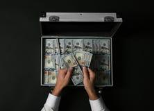 Affärsman som räknar pengar över resväskan på mörk bakgrund arkivfoto