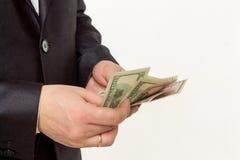 Affärsman som räknar pengar på en vit bakgrund royaltyfria foton
