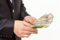 Affärsman som räknar pengar på en vit bakgrund arkivbilder