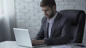 Affärsman som reagerar till emailen på bärbara datorn som grubblar över kommande avtal stock video