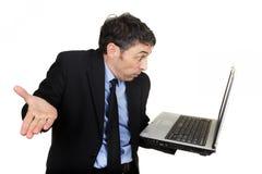 Affärsman som rycker på axlarna, som han läser hans bärbar dator Royaltyfri Fotografi