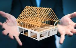 Affärsman som rymmer 3D som framför det oavslutade planhuset i hans mummel Royaltyfri Bild