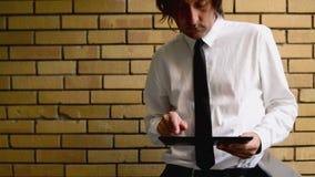 Affärsman som rymmer den digitala minnestavladatoren som står på kontorsbalkongen med den gula tegelstenväggen lager videofilmer