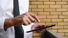 Affärsman som rymmer den digitala minnestavladatoren som står på kontorsbalkongen med den gula tegelstenväggen stock video