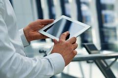 Affärsman som rymmer den digitala minnestavlan Arkivbild