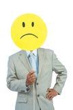 Affärsman som rymmer den ilskna smileyframsidaballongen arkivfoto