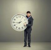 Affärsman som rymmer den stora vita klockan Royaltyfri Fotografi