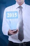 Affärsman som rymmer den tekniskt avancerade smartphonen Arkivfoton