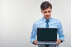 Affärsman som rymmer en bärbar dator mot en vit bakgrund Arkivbild