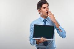 Affärsman som rymmer en bärbar dator mot en vit bakgrund Royaltyfri Foto
