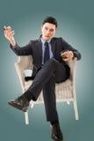 Affärsman som rymmer en cigarr fotografering för bildbyråer