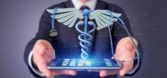 Affärsman som rymmer en 3d som redering medicinsk cadaceus och stethosco Arkivbilder