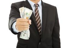 Affärsman som rymmer en handfull oss dollar arkivfoto