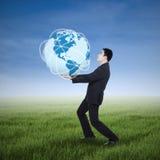 Affärsman som rymmer en jordplanet Fotografering för Bildbyråer