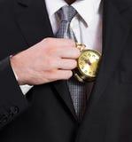 Affärsman som rymmer en klocka royaltyfri fotografi
