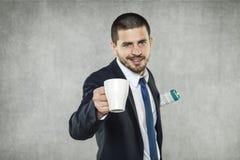 Affärsman som rymmer en kopp kaffe fotografering för bildbyråer