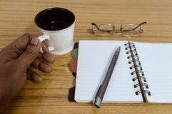 Affärsman som rymmer en kopp kaffe Affärsfackstadsplanerare med en monokel och en penna som är klara att notera en tidsbeställnin royaltyfri bild