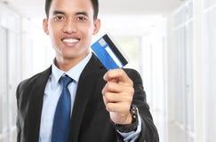 Affärsman som rymmer en kreditkort och ett leende arkivfoto