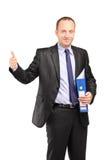 Affärsman som rymmer en mapp och ger upp tummen royaltyfria foton